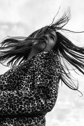 A black and white photograph of Nancy Whang. Her hair is swinging in the breeze and she's wearing leopard print.