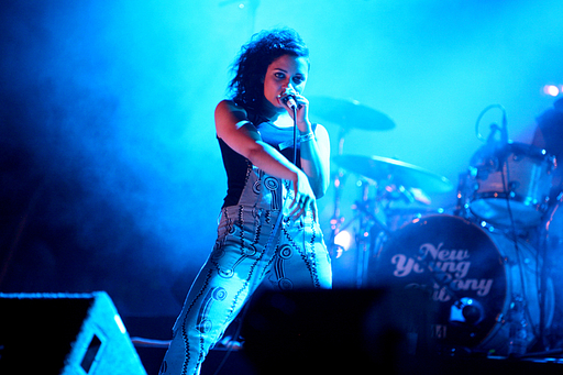 A photograph of Tahita Bulmer of New Young Pony Club in dungarees performing on stage with a microphone held to her face.
