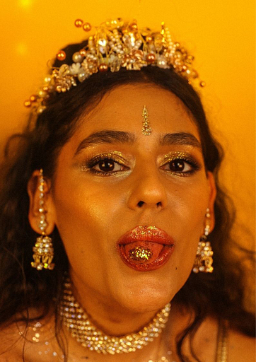 A photo of Muslim punk Nadia Javed from the Tuts. She's wearing lots of gold jewellery and is sticking her tongue out (her tongue has gold glitter on it too).