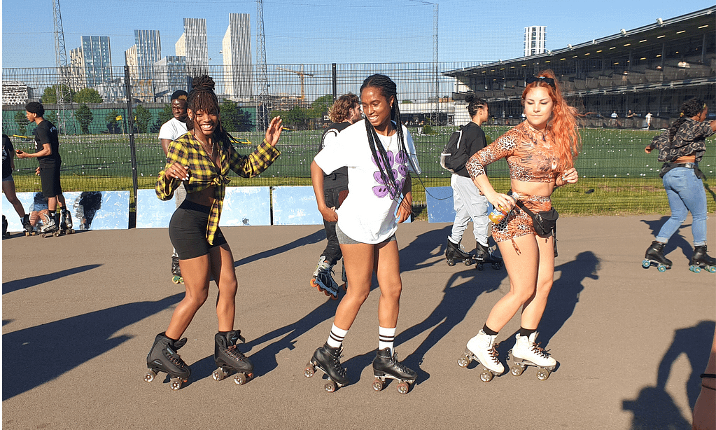 an image of three women roller skating in a row in the sun