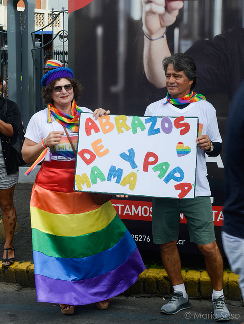 Image shows two people wrapped in pride flags, holding a sign that reads 'Abrazos de y papa mama'
