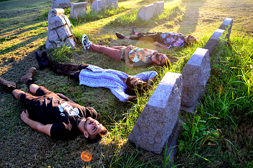 An image of Muslim punk band the Kominas lying down on the grass in a graveyard.
