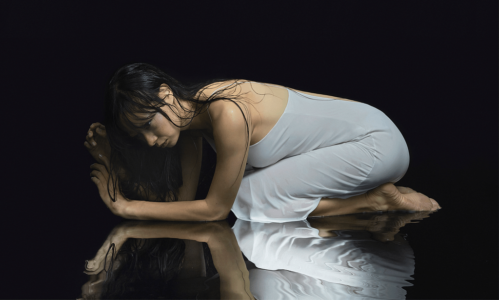 A photograph of Lucinda Chua in a white dress against a black backdrop, curled up on reflective water.