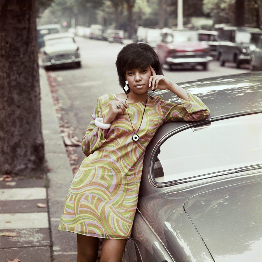 A woman leans on a car, shot by James Barnor