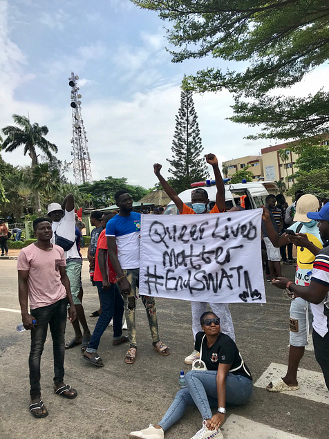 Image shows Nigerian activists standing behind a sign with raised fists. The sign reads 'Queer lives Matter #EndSARS'